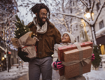African-american father and young daughter carrying gift packages home